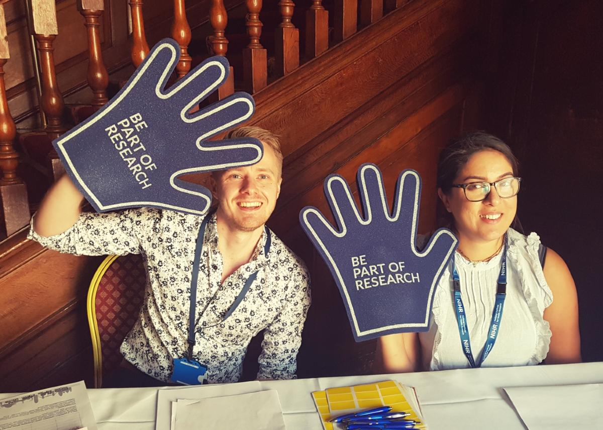 Researchers holding Take part in research foam hands