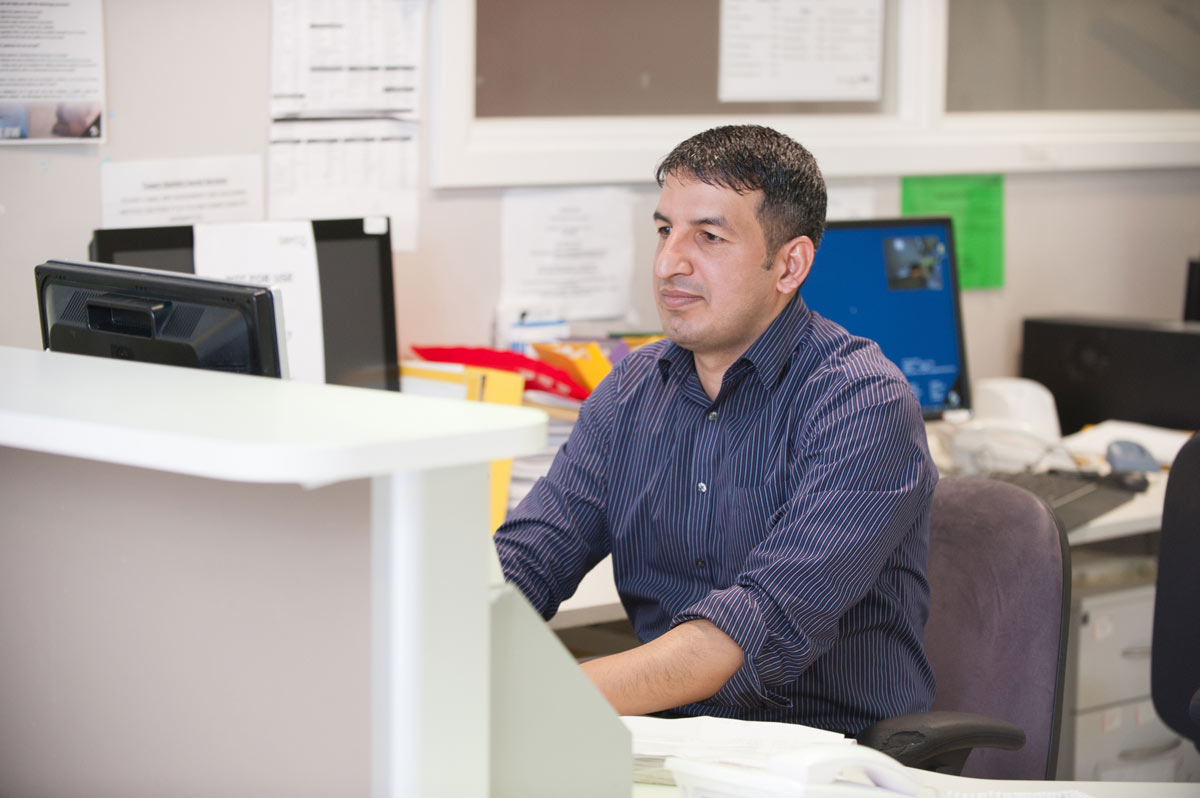 Image of a staff member behind a desk.
